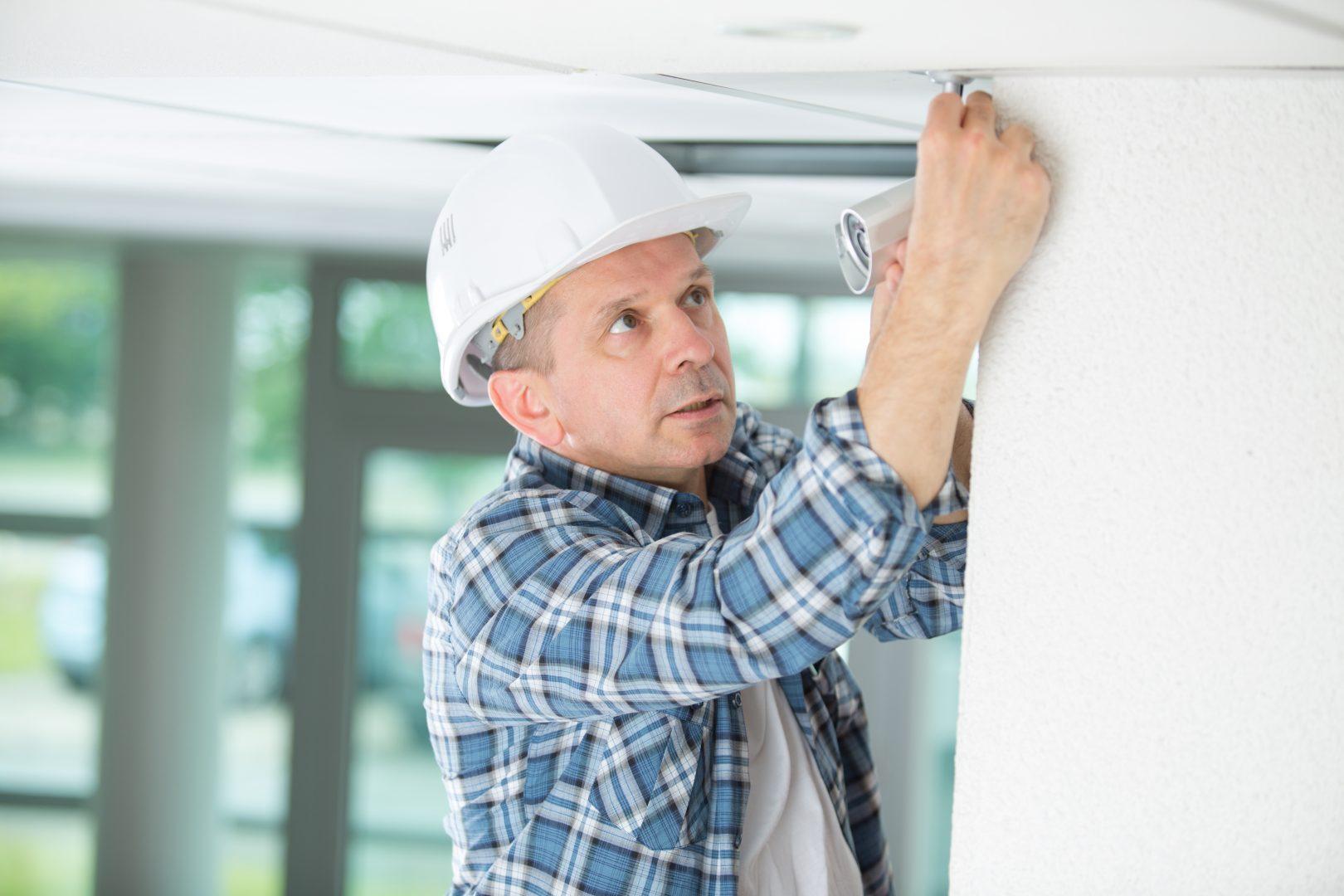 professional-electrician-replacing-the-light-bulb-PFLDF4U